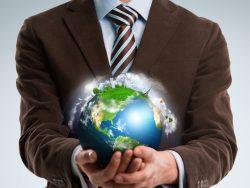 Un homme d'affaire tenant la Terre entre ses mains.