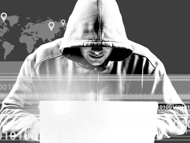 Un homme avec une capuche derrière un ordinateur portable.