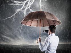 Un homme d'affaire avec des jumelles qui tient un parapluie sous un temps orageux.