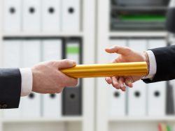 Un homme d'affaire donnant un bâton de relais à un autre homme d'affaire.