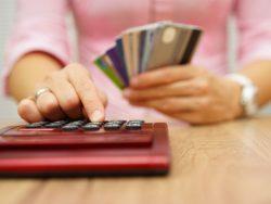 Une femme tenant trois cartes de crédit dans une main et tapant sur une calculette de l'autre.
