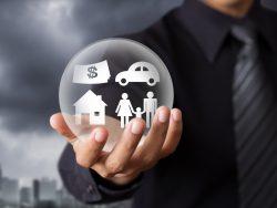 Homme d'affaire tenant une boule où sont représentés les piliers de l'assurance: automobile, immobilier, famille et argent.