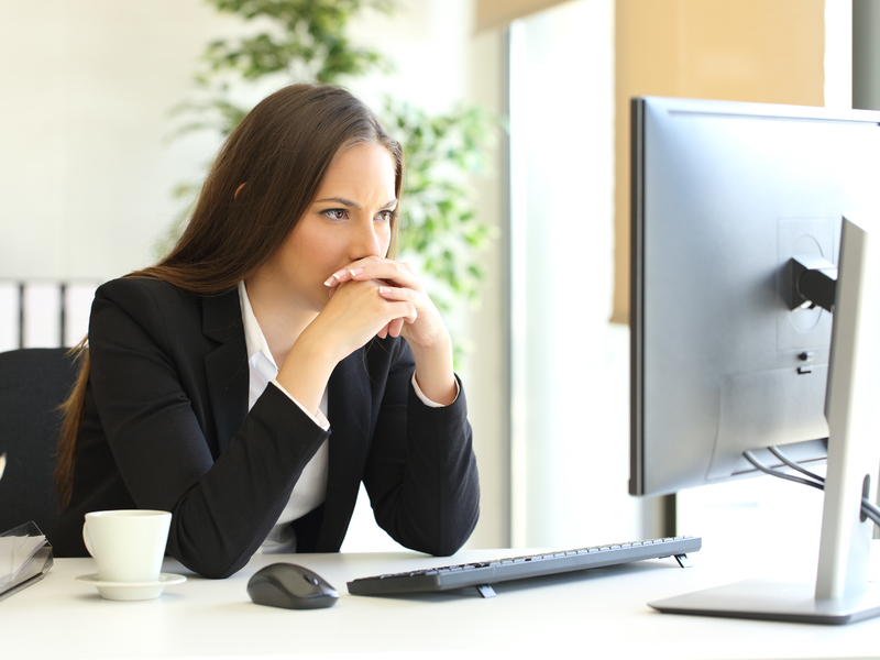 femme d'affaire réfléchit en regardant son écran d'ordinateur