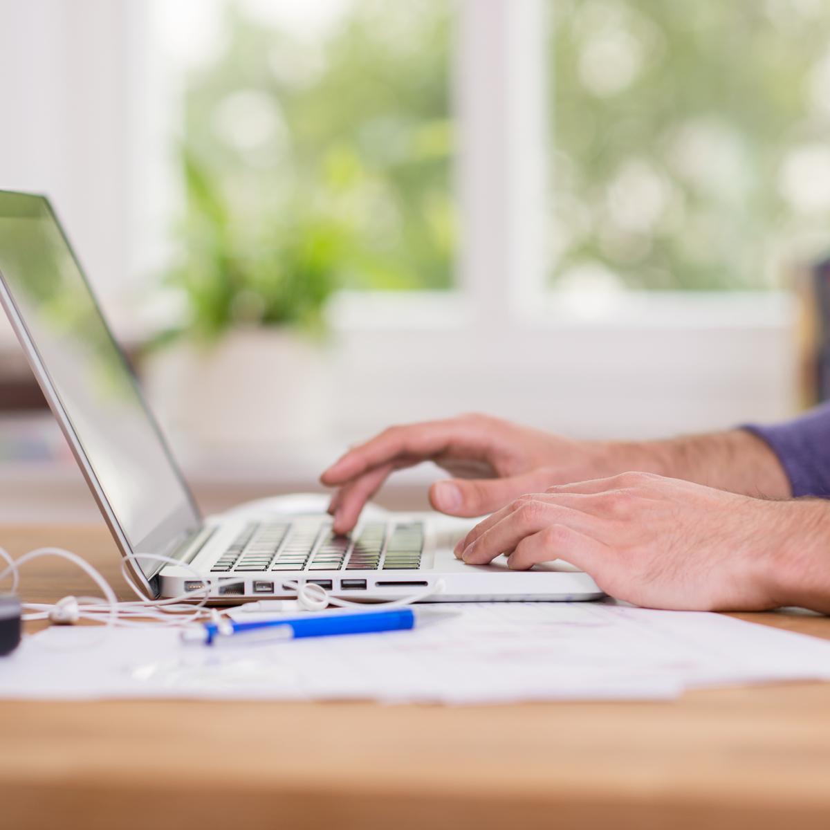 Homme à une table devant son ordinateur.
