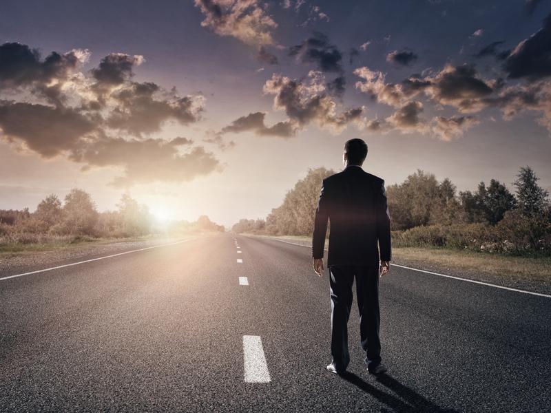 Homme d'affaire sur une route droite face à un soleil levant.