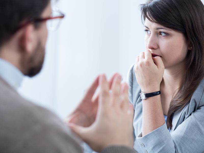 Un conseiller qui explique un sujet délicat à une jeune femme angoissée.