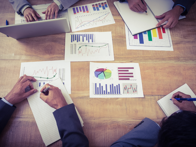 Quatre personnes autour d'une table avec pleins de graphiques financiers devant elles.