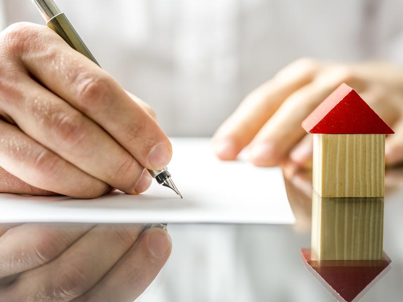 Un homme d'affaire signant un document sur une table, devant lui on voit une petite maison en bois.