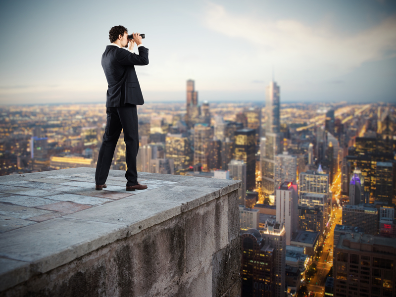 Un homme d'affaire avec des jumelles debout sur un toit d'immeuble observant l'horizon avec des jumelles.