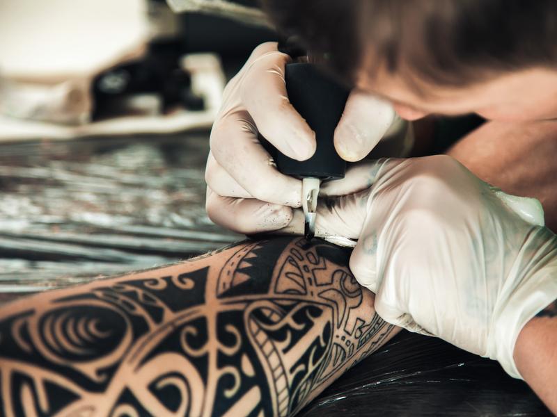 Un tatoueur qui tattoo un bras.