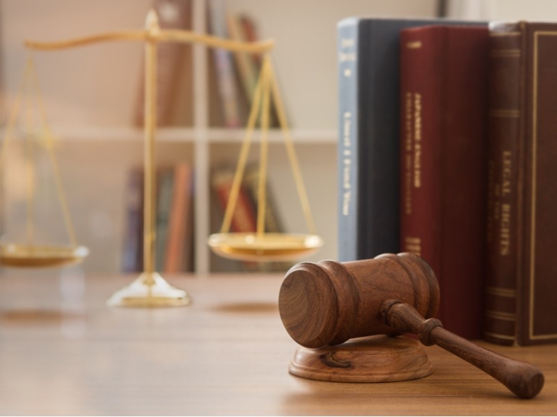 Un marteau judiciaire sur un bureau et une balance de droit avec des livres de droit à côté.