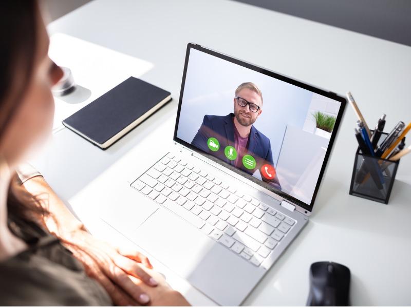Une femme devant un ordinateur qui fait une vidéoconférence avec un homme d'affaires.
