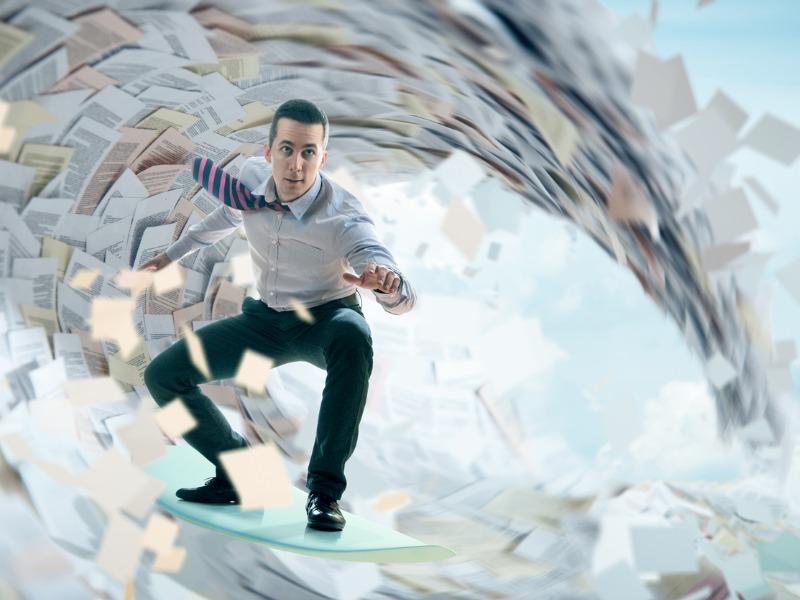Un homme d'affaires surfant sur une vague de papiers.