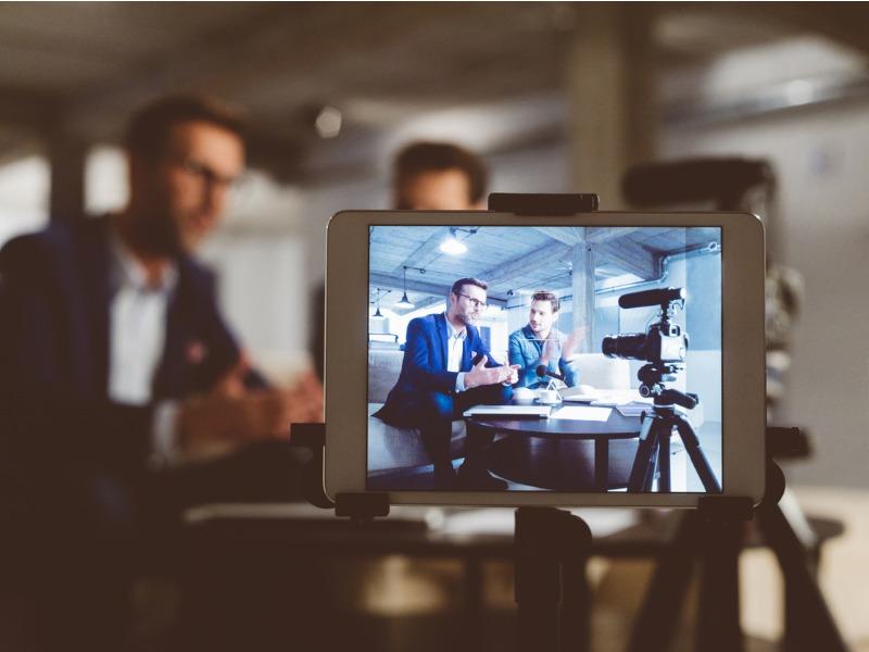 Un écran de caméra sur lequel on voit deux businessman assis à une table.