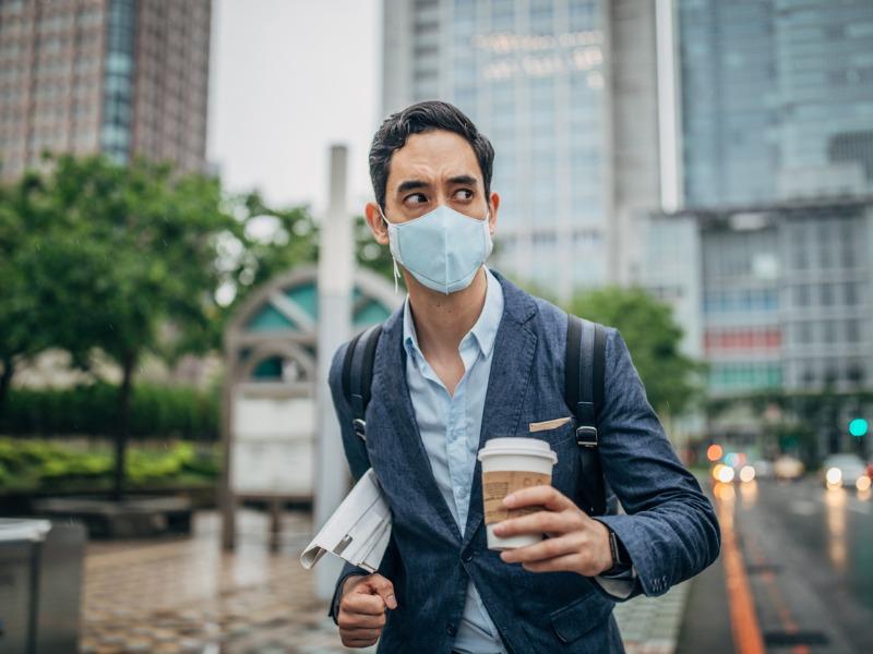 Un homme d'affaires portant un masque. Il a également un café et un journal dans les mains.